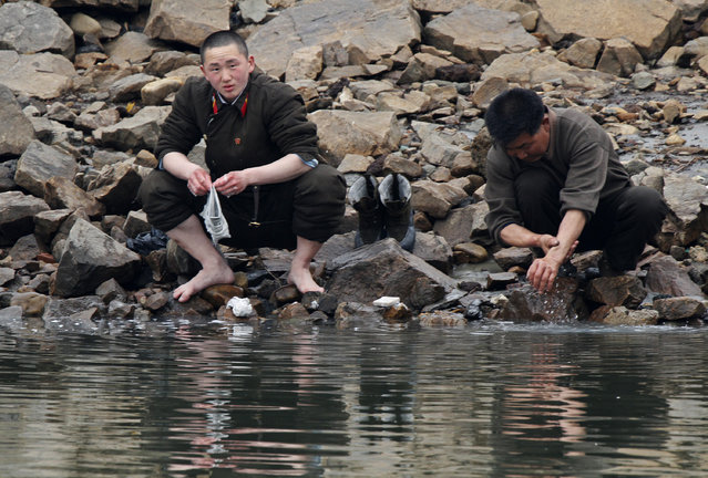 A North Korean soldier washes his socks as his comrade washes his hands at the banks of Yalu River, near the North Korean town of Sinuiju, opposite the Chinese border city of Dandong, April 8, 2013. (Photo by Jacky Chen/Reuters)
