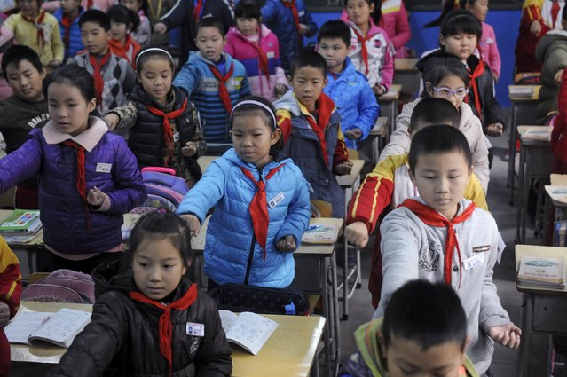 Primary school students exercise inside a classroom on a hazy day in Jinan, Shandong province, China, November 12, 2015. Most outdoor activities were banned for students due to yellow alert of smog in Jinan on Thursday, local media reported. (Photo by Reuters/Stringer)