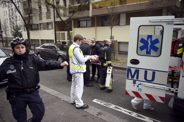 Firefighters carry an injured man on a stretcher in front of the offices of the French satirical newspaper Charlie Hebdo in Paris on January 7, 2015. (Photo by Martin Bureau/AFP Photo)