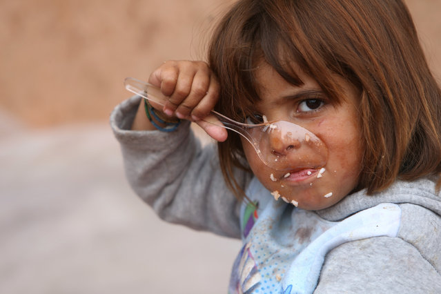 A child who recently fled the Islamic State's stronghold on the outskirts of Mosul eats at Debaga camp, on the outskirts of Erbil, Iraq October 28, 2016. (Photo by Alaa Al-Marjani/Reuters)