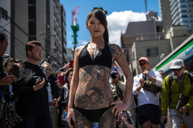 A heavily tattooed Japanese woman poses for photographs near Asakusa Temple during the third and final day of Sanja Festival, on May 20, 2018 in Tokyo, Japan. Sanja Festival is one of Japan's major festivals and is held annually in the Asakusa area of Tokyo. The three day event starts with a grand parade with people in traditional costumes performing dances before around a hundred mikoshi (portable shrines) from the local communities are carried to and from Asakusa Temple watched on by an audience of locals and tourists. (Photo by Carl Court/Getty Images)