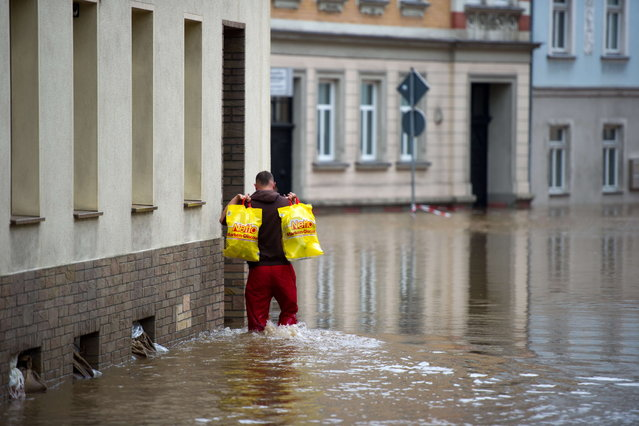 A man carrying plastic bags makes his way through a overfloode street in Doebeln, eastern Germany, on June 3, 2013. Parts of the eastern and southern Germany were flooded due to heavy and ongoing rainfalls. (Photo by Arno Burgi/AFP Photo)