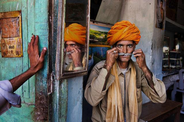 A man in an orange turban, pictured in Rajasthan, 2009. (Photo by Steve McCurry)