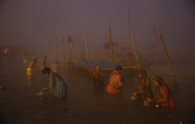 "Hindu devotees bathe early morning at Sangam, the confluence of rivers Ganges and Yamuna, to mark Makar Sankranti festival during the annual traditional fair of ""Magh Mela"" in Allahabad, India, Wednesday, January 14, 2015. (Photo by Rajesh Kumar Singh/AP Photo)"