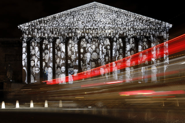 Cars pass by the national assembly in Paris, where a projection of French artist JR is displayed as part of the 2015 Paris Climate Conference, Sunday, November 29, 2015. More than 140 world leaders are gathering in Paris for high-stakes climate talks that start Monday, and activists are holding marches and protests around the world to urge them to reach a strong agreement to slow global warming. (Photo by Laurent Cipriani/AP Photo)