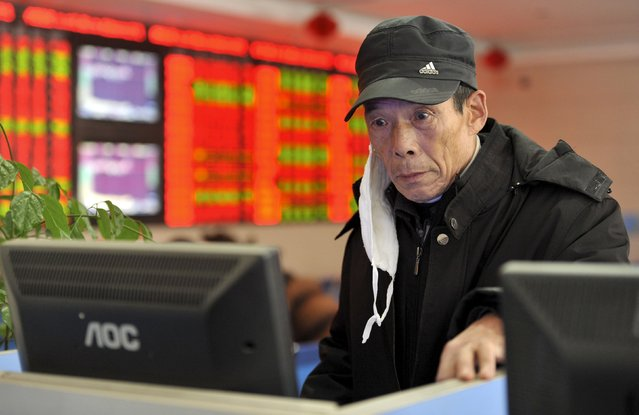 An investor with a face mask looks at a computer screen showing stock information at a brokerage house in Fuyang, Anhui province, China, December 1, 2015. (Photo by Reuters/Stringer)