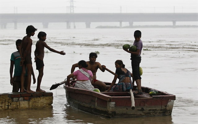 A man ferries his boat after retrieving floating watermelons from the flooded waters of river Yamuna in New Delhi June 18, 2013. The rains are at least twice as heavy as usual in northwest and central India as the June-September monsoon spreads north, covering the whole country a month faster than normal. (Photo by Anindito Mukherjee/Reuters)