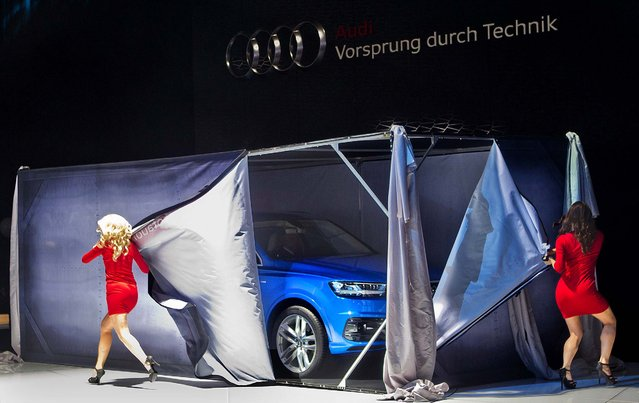 Models peel the sides away of a box unveiling the new Audi Q7 SUV inside, at the North American International Auto Show, Monday, January 12, 2015, in Detroit. (Photo by Tony Ding/AP Photo)