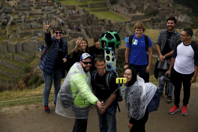 Daniel Filip, Tech Lead Manager for Google Maps, poses with tourists, as he carries the Trekker, a 15-camera device, while mapping the Inca citadel of Machu Picchu for Google Street View in Cuzco, Peru, August 12, 2015. (Photo by Pilar Olivares/Reuters)