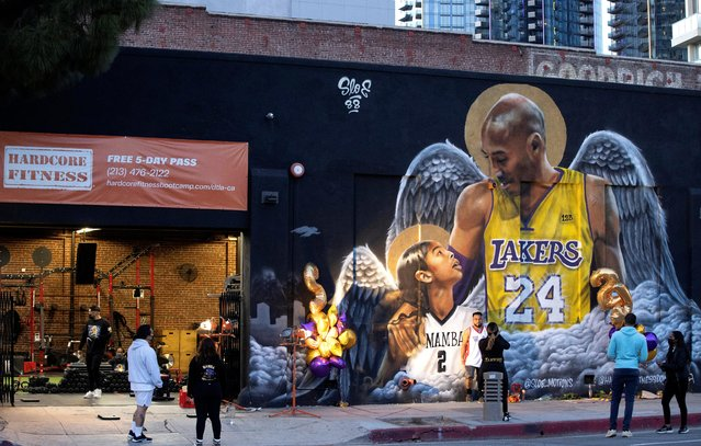 People stop by a mural of late Kobe Bryant, who died one year ago alongside his daughter and seven others when their helicopter crashed into a hillside, in Los Angeles, California, January 26, 2021. (Photo by Mario Anzuoni/Reuters)