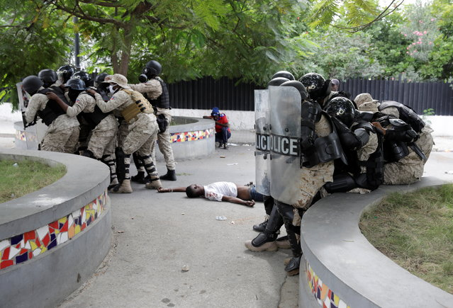 Haitian National Police (PNH) officers take position next to a dead body during clashes with protestors at a demonstration demanding the resignation of Haiti's President Jovenel Moise, at the 217th anniversary of the Battle of Vertieres, the last major battle of Haitian independence from France, in Port-au-Prince, Haiti, November 18, 2020. (Photo by Andres Martinez Casares/Reuters)