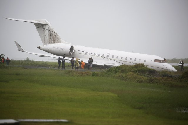 People gather around a plane that skidded off the runaway of Tacloban's airport, January 17, 2015. Senior cabinet and security officials of President Benigno Aquino administration are all safe after a plane carrying them overshoot the runway and skidded to a grassy area as the plane was taking off at Tacloban airport on Saturday, media reports said. The officials attended a mass by Pope Francis who cut short his visit due to a storm. (Photo by Damir Sagolj/Reuters)