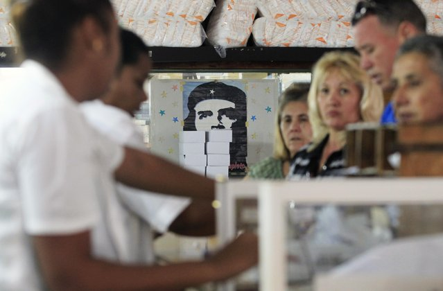 """Customers queue in a store near an image of late revolutionary hero Ernesto """"Che"""" Guevara in downtown Havana January 20, 2015. (Photo by Reuters/Stringer)"""