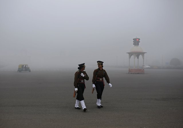 Indian soldiers walk before the start of their rehearsal for the Republic Day parade on a foggy winter morning in New Delhi January 16, 2015. (Photo by Ahmad Masood/Reuters)