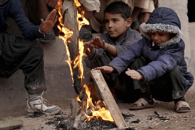 Children warm themselves around a fire to beat the cold weather at a road side in Peshawar, Pakistan, 20 January 2021. Reports state that many cities in Pakistan are experiencing unusual cold weather conditions during which regular daytime temperatures fall around five degree Celsius in wide parts of the country. (Photo by Bilawal Arbab/EPA/EFE)