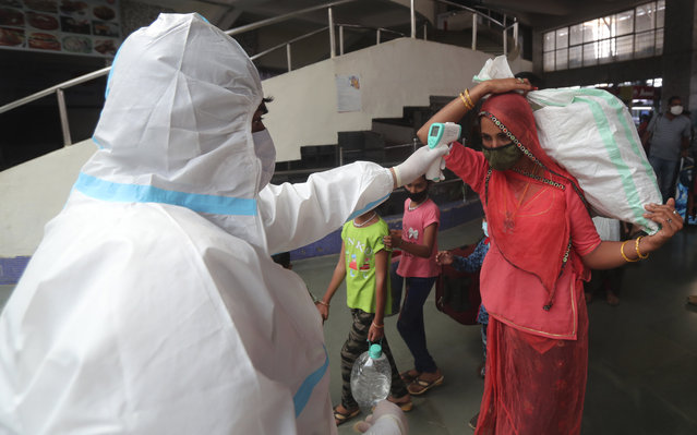 A health worker checks the temperature of a passenger at Bandra train station in Mumbai, India, Wednesday, February 17, 2021. Health officials have detected a spike in COVID-19 cases in several pockets of Maharashtra state, including in Mumbai, the country's financial capital. (Photo by Rafiq Maqbool/AP Photo)