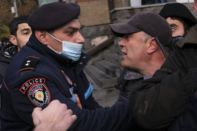 A police officer tries to detain demonstrators during a rally demanding the resignation of the country's prime minister over his handling of the conflict with Azerbaijan over Nagorno-Karabakh in Yerevan, Armenia, Tuesday, December 8, 2020. Armenian opposition politicians and their supporters have been calling for Prime Minister Nikol Pashinyan to step down ever since he signed a peace deal that halted 44 days of deadly fighting over the separatist region, but called for territorial concessions to Azerbaijan. (Photo by Hrant Khachatryan/AP Photo)