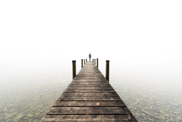 A man stands at the end of a landing stage during morning mist at lake Starnberg, southern Germany, Tuesday, November 11, 2014. (Photo by Andreas Weihmayr/AP Photo/DPA)
