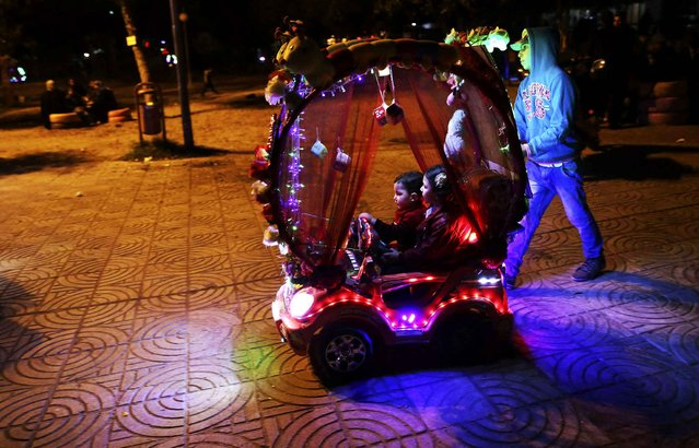 Palestinian children ride an electronic toys car while touring at the main square in Gaza City, Thursday, December 17, 2015. (Photo by Adel Hana/AP Photo)