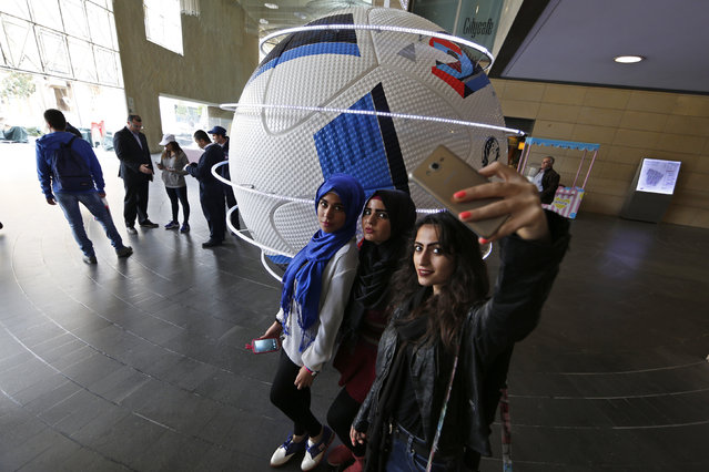 """Youth take pictures in front of a decorated giant UEFA Euro 2016 soccer ball, dubbed """"Beau Jeu"""" (Beautiful Game), in downtown Beirut, Lebanon December 17, 2015. (Photo by Jamal Saidi/Reuters)"""
