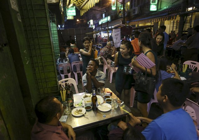 People drink beer in 19th street, also known as Yangon beer street, in Yangon December 8, 2015. Myanmar Brewery Limited (MBL), the military-linked producer of the old favourite Myanmar Beer and four other brands, faces stiff competition from global giants for a rapidly growing consumer market set to lift beer consumption from among Asia's lowest. (Photo by Soe Zeya Tun/Reuters)
