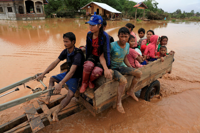 People sit on a locally made vehicle as they travel during the flood after the Xepian-Xe Nam Noy hydropower dam collapsed in Attapeu province, Laos on July 26, 2018. (Photo by Soe Zeya Tun/Reuters)