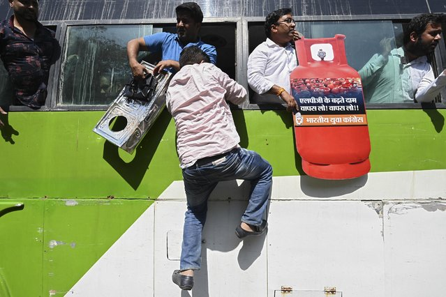 An activist of the Indian Youth Congress (IYC) escapes thorugh a window of the bus after he was detained by police during a protest against the recent price hike of fuel and Liquefied Petroleum Gas (LPG) outside the Ministry of Petroleum and Natural Gas in New Delhi on March 2, 2021. (Photo by Money Sharmaa/AFP Photo)
