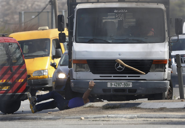 A truck driven by a Palestinian man runs over an Israeli man as a stick he was wielding is thrown into the air at Fawar junction near the West Bank city of Hebron, October 20, 2015. The Israeli, who later died, had gotten out of his car after Palestinian demonstrators threw stones at it and began to hit passing Palestinian cars with the stick. (Photo by Nasser Shiyoukhi/AP Photo)