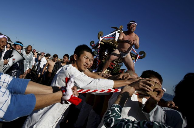 """Man wearing the traditional """"fundoshi"""" or loincloth rides on a """"mikoshi"""" or portable shrine as local people carry it into the sea during a festival to wish for calm waters in the ocean and good fortune in the new year in Oiso, Kanagawa prefecture, west of Tokyo, Japan, January 1, 2016. (Photo by Yuya Shino/Reuters)"""