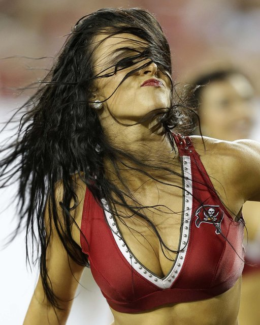 A Tampa Bay Buccaneers cheerleader performs during a preseason game against the Baltimore Ravens in Tampa. (Photo by Chris O'Meara)/Associated Press)
