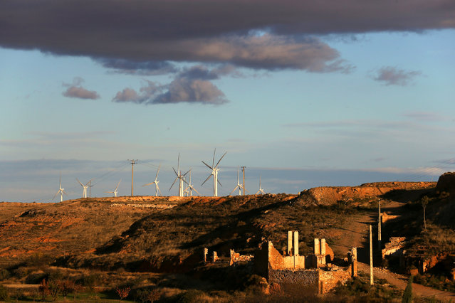 Windmills are seen behind the ruins of the old village of Belchite, in northern Spain, November 13, 2016. (Photo by Andrea Comas/Reuters)
