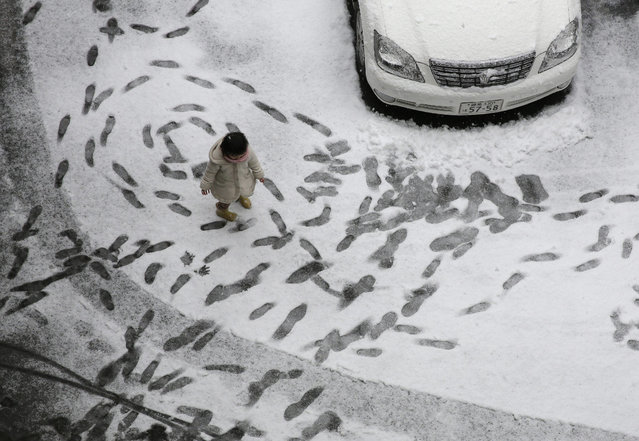 A little girl enjoys to mark her footprints on a snow covered parking lot in Tokyo, Japan, 30 January 2015. It was expected the snowfall in central Japanese capital will be five-centimeters in the morning. (Photo by Kimimasa Mayama/EPA)