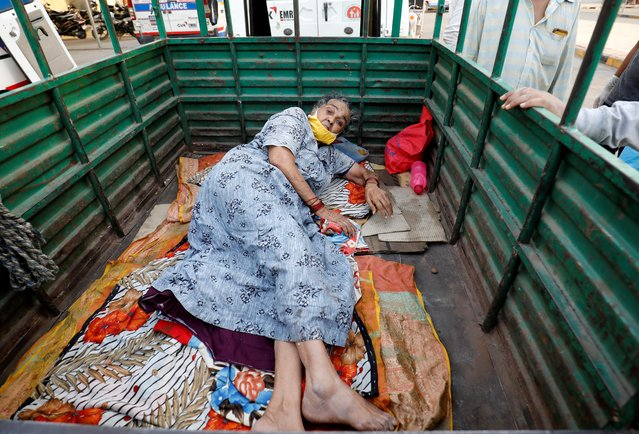 A woman lies in the back of a load carrier waiting to enter a COVID-19 hospital for treatment, amidst the spread of the coronavirus disease (COVID-19), in Ahmedabad, India, April 26, 2021. (Photo by Amit Dave/Reuters)
