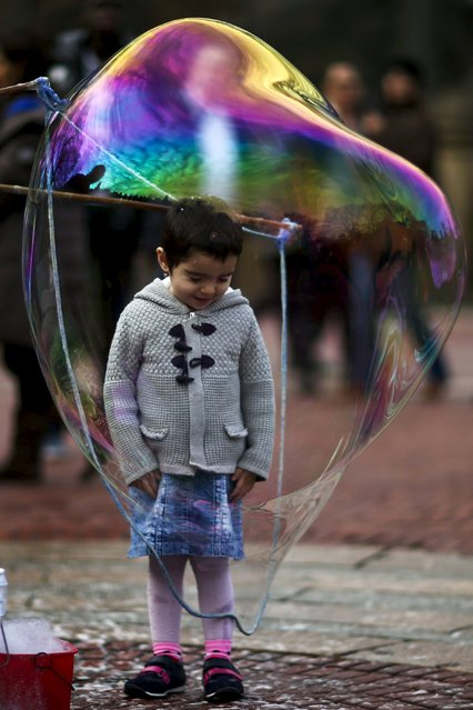 A child goes inside a bubble during a warm day in Central Park, New York December 25, 2015. (Photo by Eduardo Munoz/Reuters)
