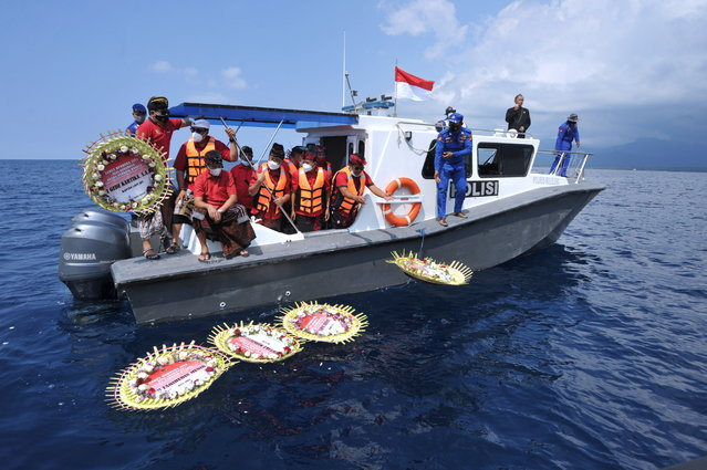 People throw flowers and petals with names of the sunken KRI Nanggala-402 submarine crew members from the boat during a prayer at the sea near Labuhan Lalang, Bali, Indonesia on April 26, 2021. (Photo byFikri Yusuf/Antara Foto via Reuters)