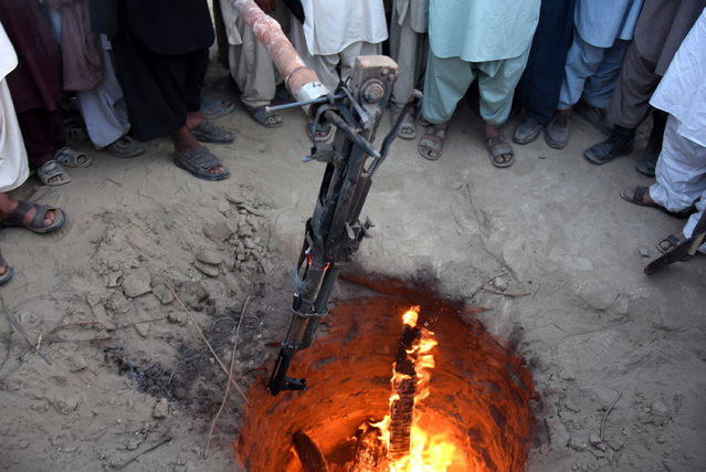 A Kalashnikov is thrown in a fire as a symbol to end enmities among different tribes in Balochistan province during a Tribal Jirga (meeting) in Qila Abdullah, Pakistan, 10 September 2018. Hundreds of Tribal elders from different Tribes of Balochistan gathered in Qila Abdullah to find ways to reduce tensions among different tribes and to end decades long enmities and feuds among different tribes that has claimed thousands of lives in last many years. (Photo by Jamal Taraqai/EPA/EFE)