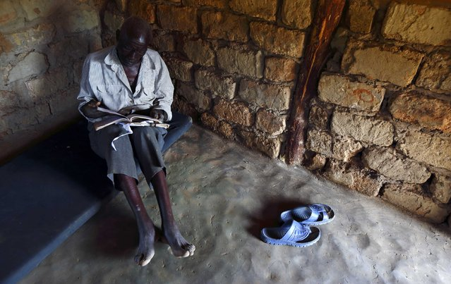 HIV-positive 71-year-old Sylverio Hachiploa reads in his thatched hut during a visit by a home-based care team in the village of Nedwmba, south of the Chikuni Mission in the south of Zambia February 23, 2015. (Photo by Darrin Zammit Lupi/Reuters)