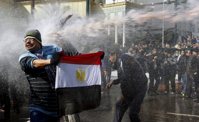 A protester holds an Egyptian flag as he stands in front of water cannons during clashes in Cairo January 28, 2011. (Photo by Yannis Behrakis/Reuters)