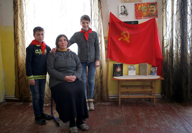 """Natia Babunashvili, 40, an unemployed mother of two, poses for a portrait with her children Tamuna (R), 14, and Giorgi, 13, at her home in Tbilisi, Georgia, November 24, 2016. """"My father was a party boss in one of the regions of Soviet Georgia and he taught me to love Stalin from childhood"""", Babunashvili said. """"I tell my children of my childhood during Soviet times...how good my life was, how happy I was in the USSR. They form their own opinions but they share my views for now"""". (Photo by David Mdzinarishvili/Reuters)"""