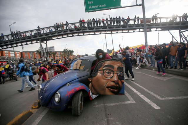 People push a car with the image of late Colombian humorist and journalist Jaime Garzon painted on it during a protest demanding government action to tackle poverty, police violence and inequalities in healthcare and education systems, in Bogota, Colombia, June 2, 2021. (Photo by Luisa Gonzalez/Reuters)