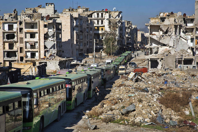 Buses are seen during an evacuation operation of rebel fighters and their families  from rebel-held neighbourhoods in the embattled city of Aleppo on December 15, 2016. A convoy of ambulances and buses left rebel territory in Aleppo in the first evacuations under a deal for opposition fighters to leave the city after years of fighting. The rebel withdrawal will pave the way for President Bashar al-Assad's forces to reclaim complete control of Syria's second city, handing the regime its biggest victory in more than five years of civil war. (Photo by Karam Al-Masri/AFP Photo)