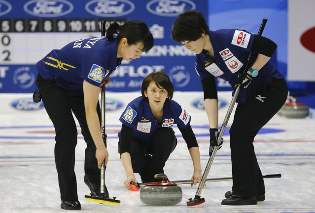 Japan's third Sayaka Yoshimura (C) watches as her team mates Anna Ohmiya (L) and Kaho Onodera sweep during their curling round robin game against Switzerland at the World Women's Curling Championships in Sapporo March 14, 2015. (Photo by Thomas Peter/Reuters)