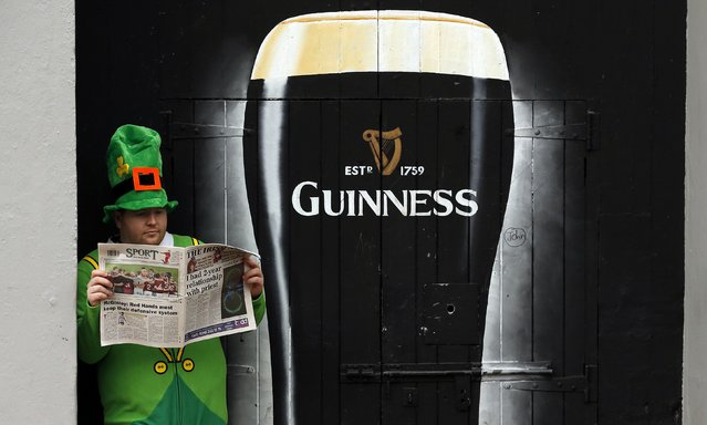 A man dressed as a Leprechaun reads a newspaper during St Patrick's Day festivities in the city of Londonderry March 17, 2015. (Photo by Cathal McNaughton/Reuters)