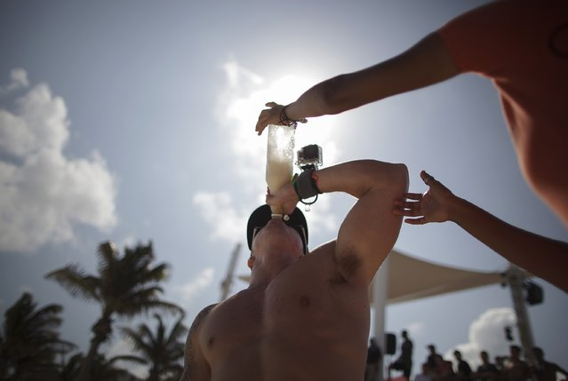 A spring breaker drinks from a bottle during games held at a beach in Cancun March 7, 2015. Florida has long struggled with the crowds of rowdy students embracing its sun, sea and party life in March and April. Fort Lauderdale announced on television in 1985 that spring breakers were no longer welcome after 350,000 students took nudity and drinking to new heights. (Photo by Victor Ruiz Garcia/Reuters)