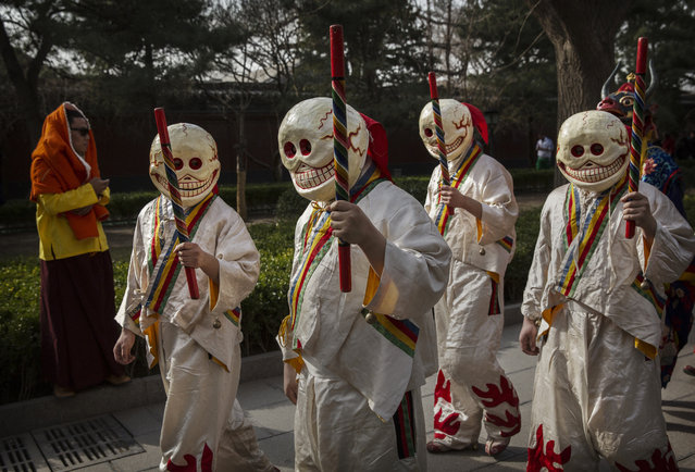 Tibetan Buddhist monks dressed as ghosts take part in the Beating Ghosts ritual at the Lama Temple, or Yonghegong on March 19, 2015 in Beijing, China. (Photo by Kevin Frayer/Getty Images)