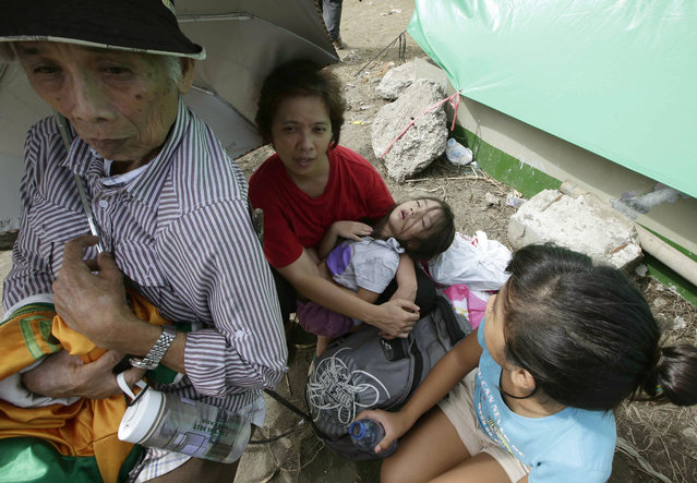 Typhoon survivors camp out at Tacloban city airport hoping to be able to board U.S. and Philippine military transport planes Wednesday, November 13, 2013, in Tacloban city, Leyte province in central Philippines. (Photo by Bullit Marquez/AP Photo)