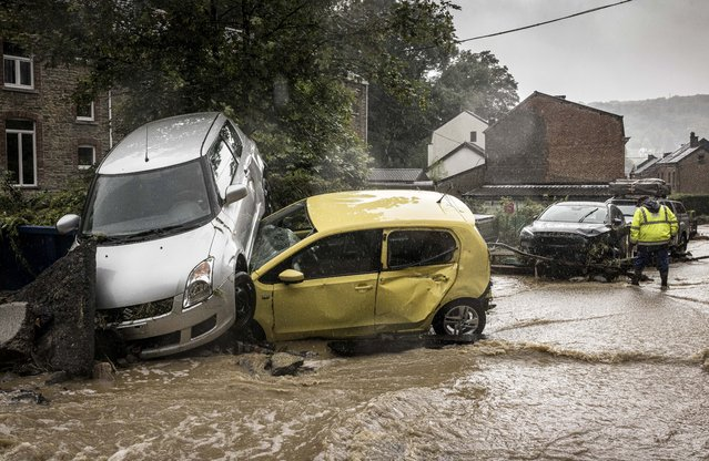 A man walks by damaged cars in a flooded street in Mery, Province of Liege, Belgium, Wednesday, July 14, 2021. A code red was issued in parts of Belgium on Wednesday as severe rains hit the area. (Photo by Valentin Bianchi/AP Photo)