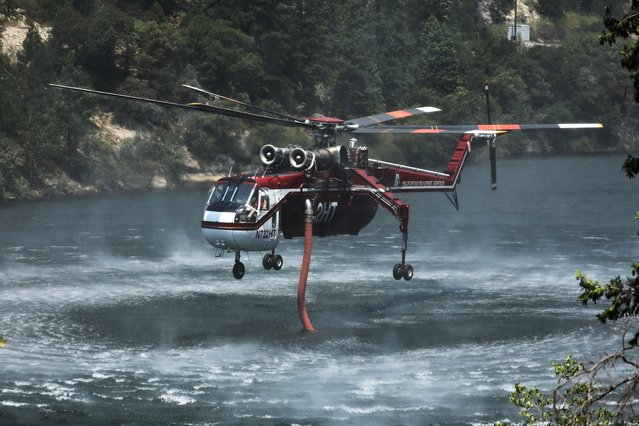 Air support gathers water from the Feather River as the Dixie Fire grows in Plumas National Forest, California, U.S., July 15, 2021. (Photo by David Swanson/Reuters)