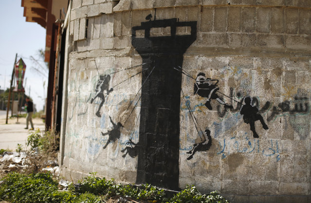A mural, presumably painted by British street artist Banksy, is seen on a wall in Biet Hanoun town in the northern Gaza Strip February 26, 2015. (Photo by Suhaib Salem/Reuters)