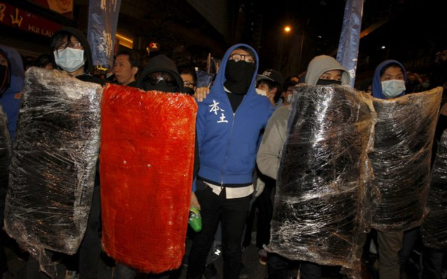 Protesters supporting illegal hawkers carry makeshift shields at Hong Kong's Mongkok shopping district, China early February 9, 2016. (Photo by Liau Chung-ren/Reuters)